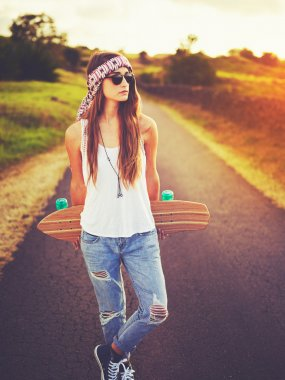Beautiful young woman with skateboard on country road at sunset stock vector