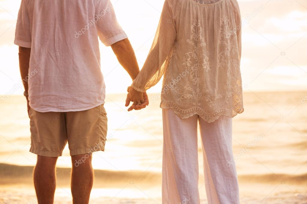 Mature Couple Holding Hands Enjoying at Sunset
