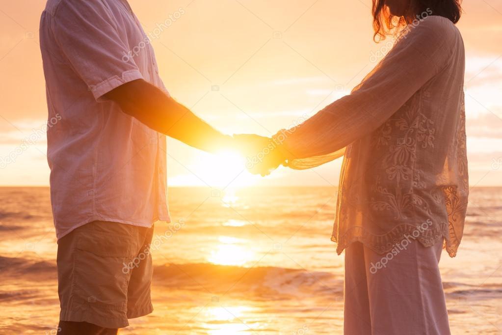 Senior Couple Holding Hands Enjoying at Sunset