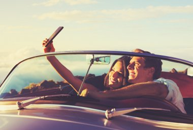 Romantic Young Couple Taking a Selfie in Classic Vintage Sports Car at Sunset stock vector