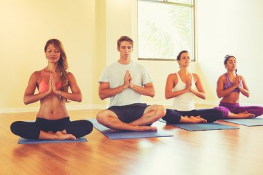 People Relaxing and Meditating in Yoga Class.