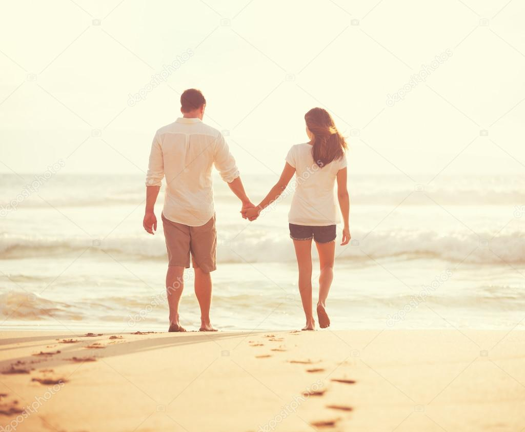 Young Lovers Walking Down the Beach at Sunset