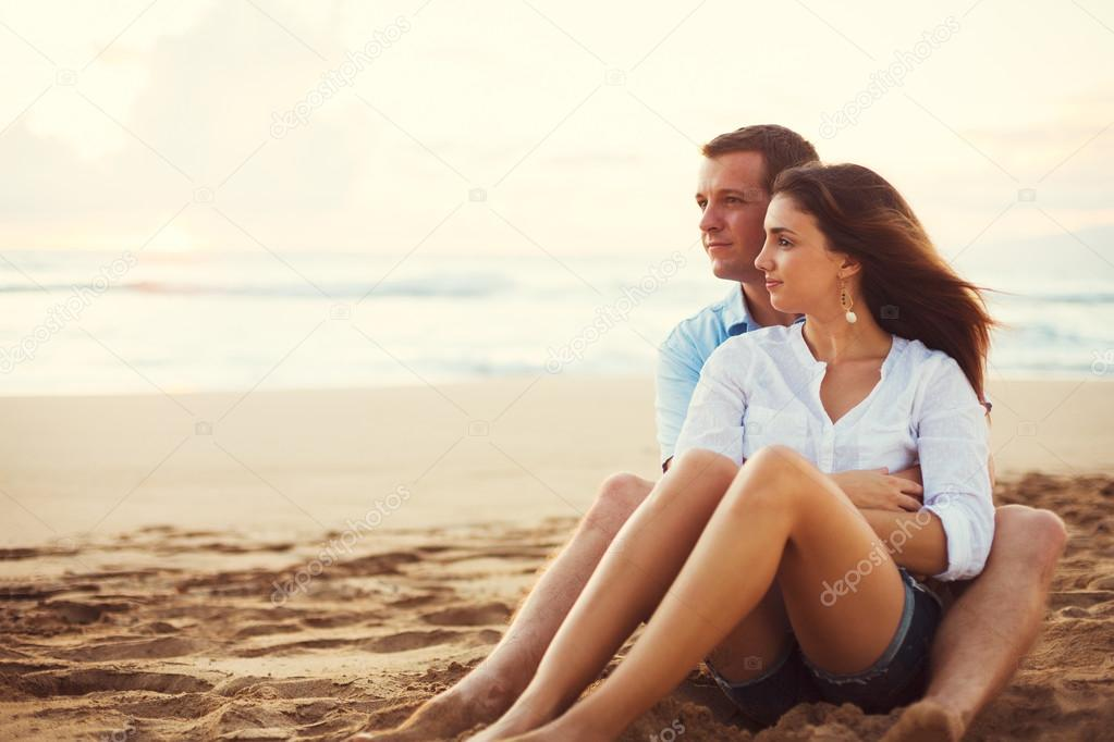 Couple Relaxing on the Beach Watching the Sunset