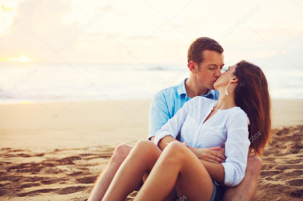 Couple Relaxing on the Beach Kissing and Watching the Sunset