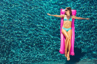 Woman Relaxing Floating on Raft in Pool