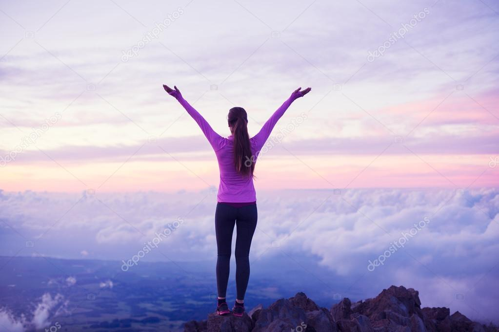 Happy Woman Hiker With Open Arms at Sunset on Mountain Peak