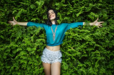 Young, attractive brunette lays back on the lush green foliage.