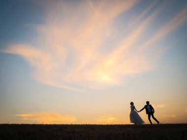Young wedding couple goes on a field on a background of red suns