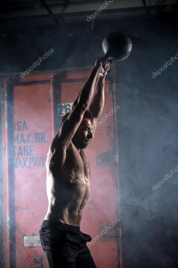 Beautiful athlete doing kettlebell swings. Profile picture. Athl ...