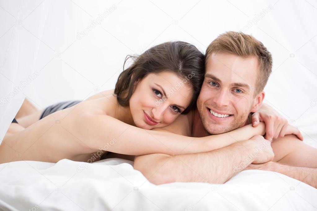 молодая парочка на белой постели