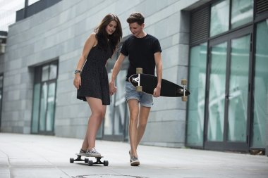Young pair in love of stylish teenagers ride longboards