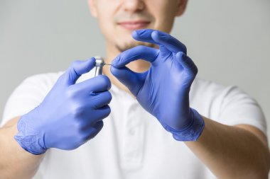 Doctor in blue latex gloves and white t-shirt holding the dental handpiece with dental bur in his hands. Studio photo on the gray background. Horizontal stock vector