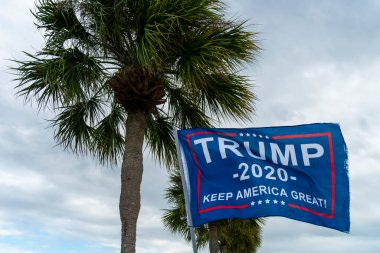 October 22, 2020 - Tarpon Springs, Florida, USA: A Trump supporter flies a flag at a local beach in Tarpon Springs, Florida