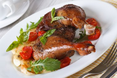 Delicious roasted duck legs with apples and arugula horizontal