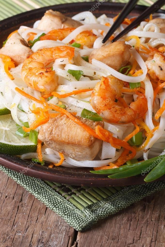 Rice noodles with seafood and chicken closeup. Vertical