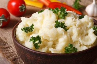 Delicious mashed potatoes with parsley closeup on the table