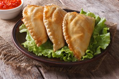 pies empanadas on a plate with lettuce and sauce, horizontal