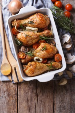 Baked chicken legs and ingredients. vertical top view
