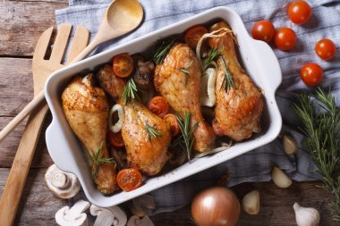 Baked chicken legs with vegetables close-up horizontal top view
