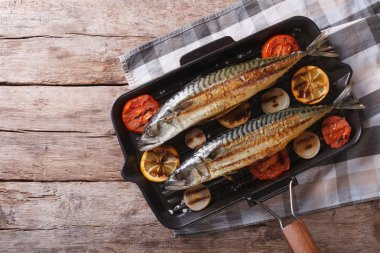 Grilled mackerel in pan with vegetables. horizontal top view
