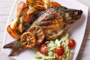 grilled fish with fried potatoes and salad horizontal top view