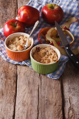 apple crumble in pots for baking on the table. Vertical