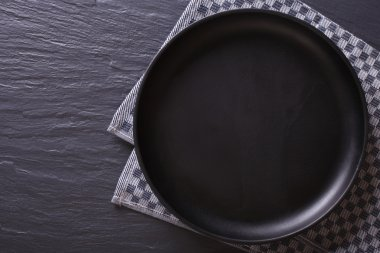 black empty plate on the table. top view horizontal