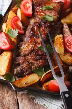 BBQ pork, potatoes and tomatoes on a grill pan. vertical top vie