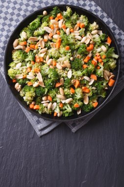 Broccoli with peanuts and carrots vertical top view
