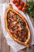 Photo Turkish pizza with meat and vegetables closeup. vertical top vie