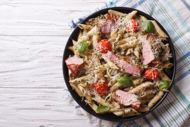 pasta with meat, parmesan, tomatoes and pesto. Horizontal top vi
