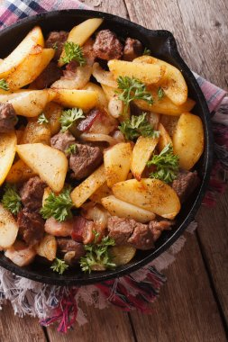 fried potatoes with meat and bacon in a pan close-up. vertical t