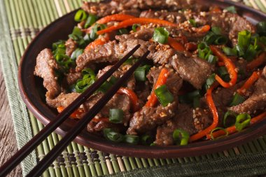 slices of beef fried with sesame seeds and carrots closeup. hori