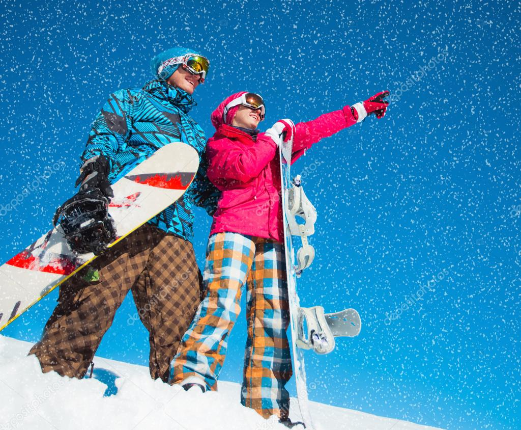 Girl and boy with snowboards on the snow