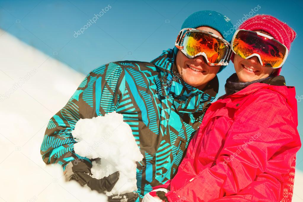 Girl and boy in winter clothes playing with sno