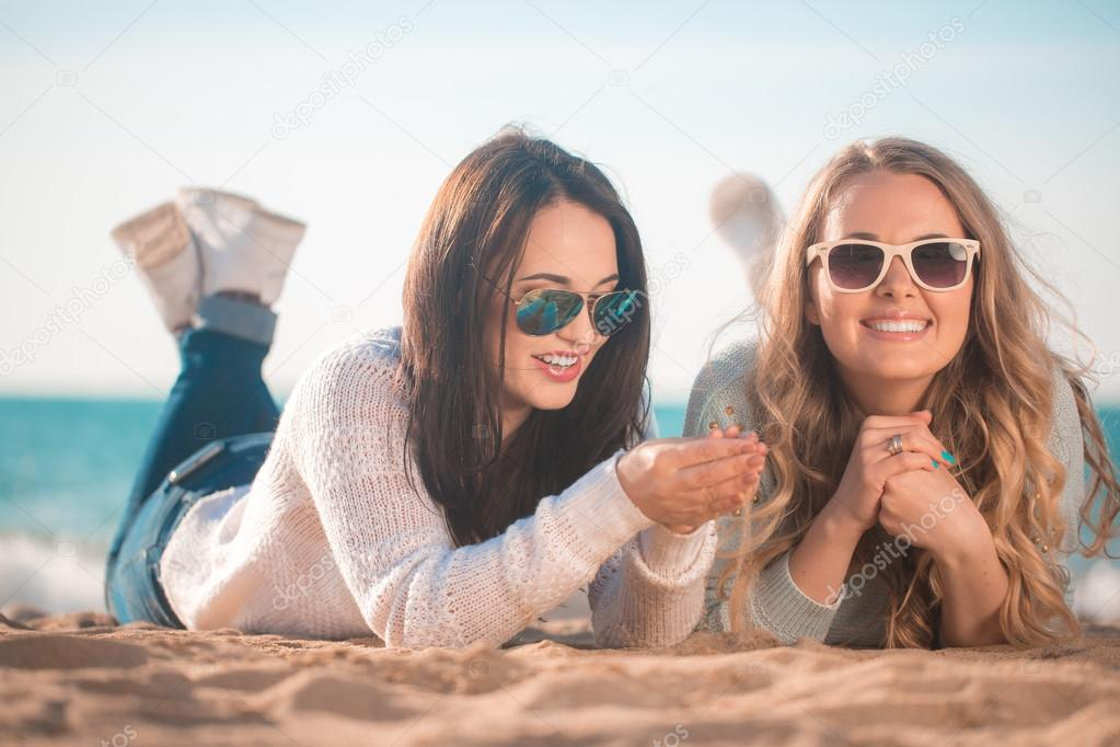 Two girlfriends resting on the beach