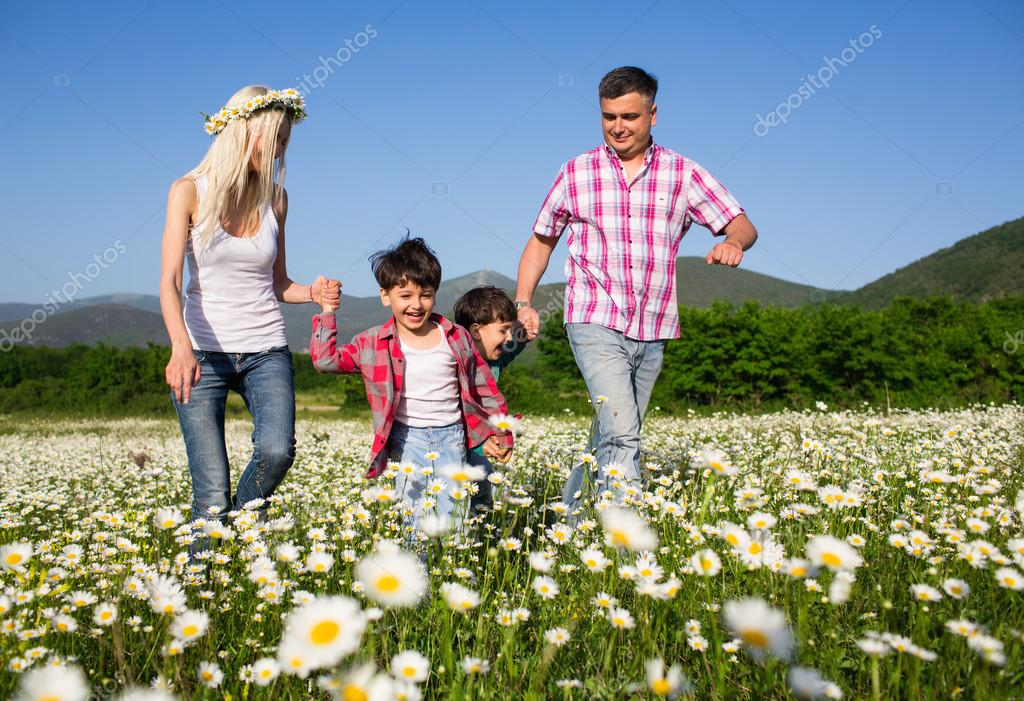 Happy family playing on the chamomile meadow stock vector