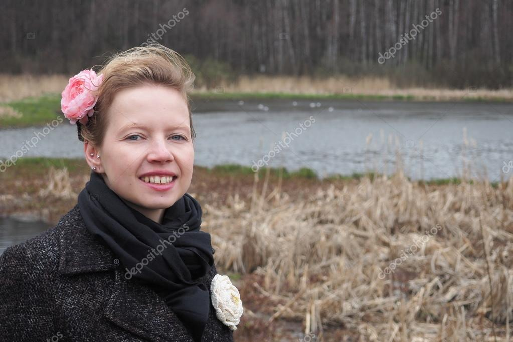 young beautiful blonde girl on the bank of the river in the dry forests