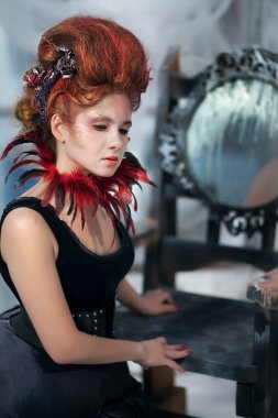 Young beautiful girl in the form of the evil fairy with red hair in a designer dress with a long skirt in unusual shoes and a necklace of feathers