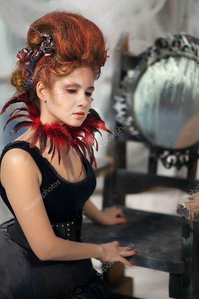 77ca04a02670f1 Jonge mooie meisje in de vorm van de boze fee met rood haar in een  ontwerper jurk met een lange rok in ongebruikelijke schoenen en een ketting  van veren ...