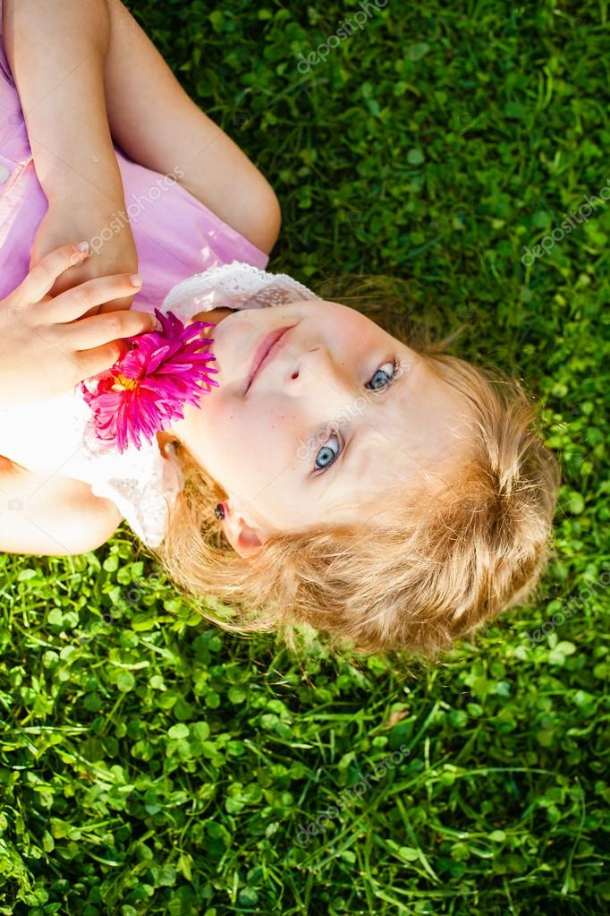 Beautiful blue-eyed blonde girl lying on the grass with a flower in the hands