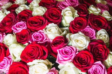 A large bouquet of white, pink and red roses