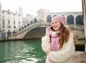 Fotografie Happy woman tourist talking cell phone in front of Rialto Bridge