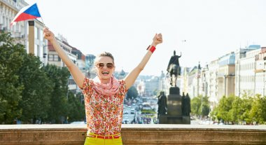 Woman with Czech flag rejoicing near National Museum in Prague