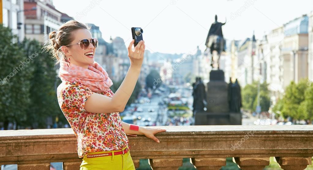 Lächelnde Frau beim Fotografieren mit Digitalkamera in