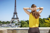 young woman relaxing in front of Eiffel tower in Paris, France