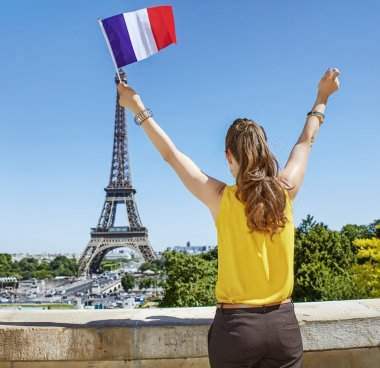 young woman rising French flag in front of Eiffel tower in Paris
