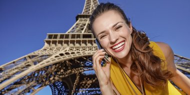 smiling young woman talking on cell phone in Paris, France