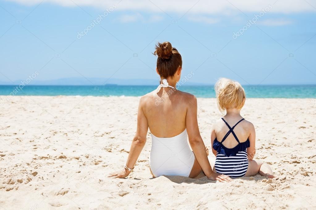 Costumi Da Bagno Per Bambino : Visto da dietro madre e bambino in costumi da bagno che si siede