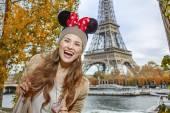 Fotografie turistické žena nosí Minnie myší uši na nábřeží v Paříži